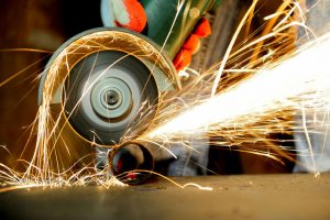 37167808 - worker cutting metal with grinder. sparks while grinding iron
